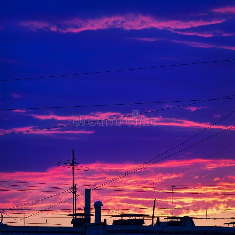 在都市屋顶的五颜六色的日落与缆绳导线和电视天线 免版税库存图片