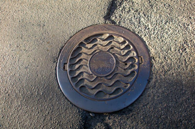 在都市柏油路的下水道出入孔 免版税库存图片