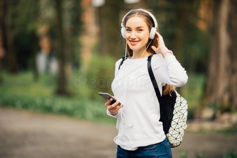 在都市背景中听到与耳机的音乐的年轻可爱的女孩画象  免版税库存图片