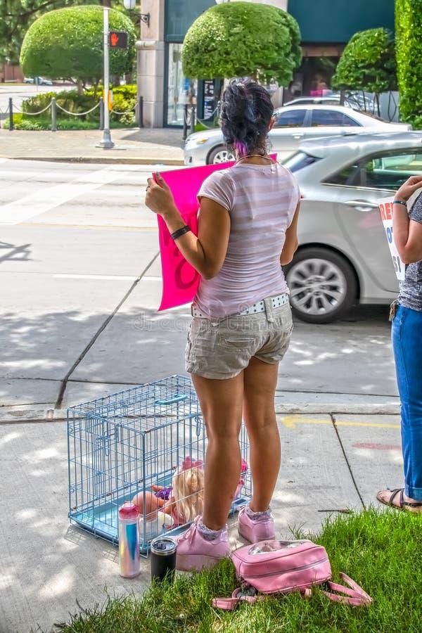 在都市街角与抗议标志和一只狗笼子的桃红色和短裤立场打扮的女孩与里面玩偶在集会反对 免版税库存照片