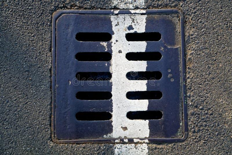 在都市路面,下水道与标号的人孔盖的方形的金属舱口盖排行 免版税库存照片