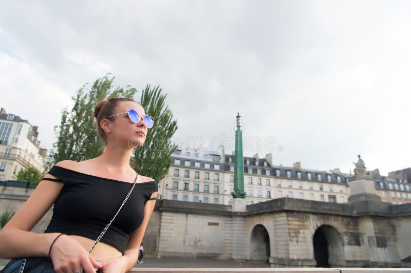 在都市风景的肉欲的女服太阳镜 性感的背心的妇女在巴黎,法国 旅行癖或假期和旅行概念 Su 库存照片