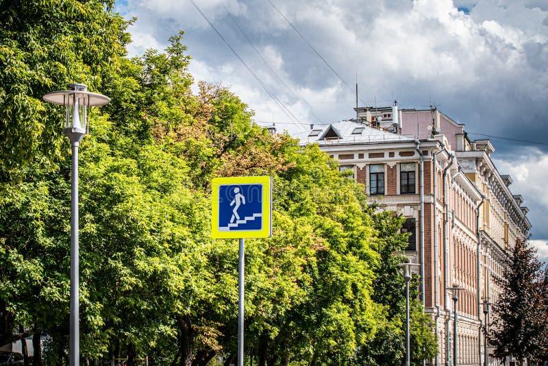 在都市风景的背景的路标步行地下过道 路灯到底、树黄绿叶子和雷暴 免版税库存图片