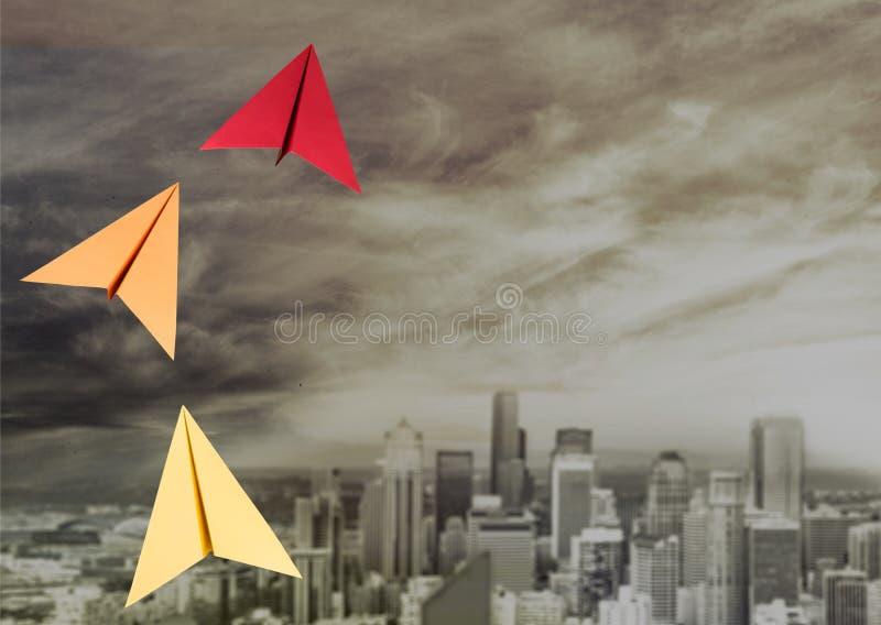 在都市风景背景的飞行的纸飞机 免版税库存图片