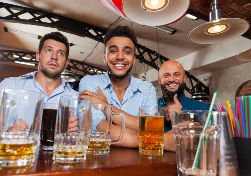 在酒吧举行玻璃愉快微笑的人小组,饮用的啤酒,混合种族快乐朋友见面 库存照片