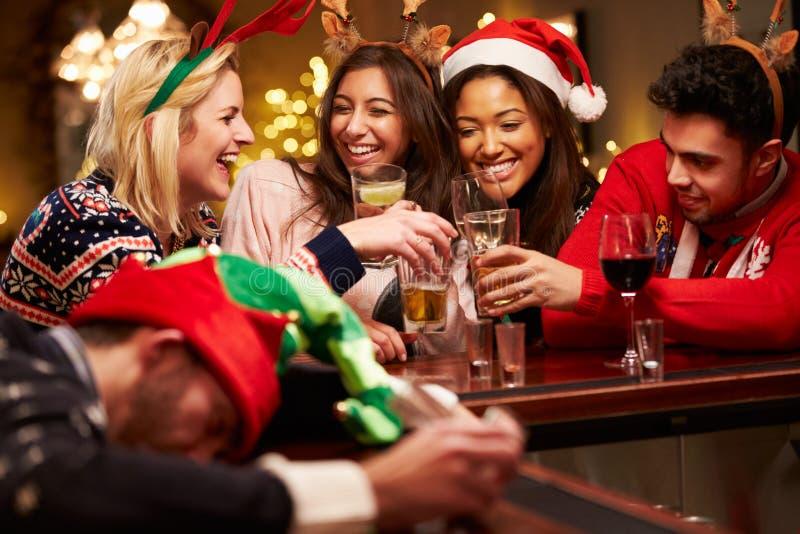 在酒吧分发的人在与朋友的圣诞节饮料期间 免版税库存图片