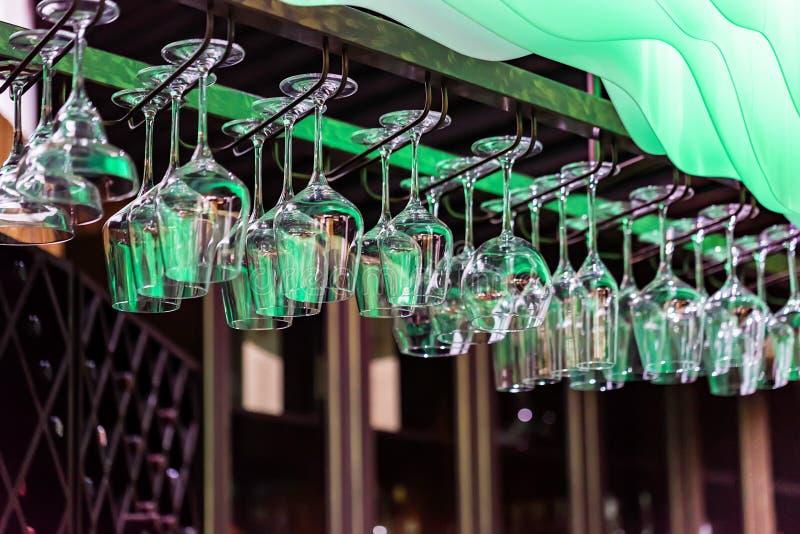 在酒吧机架的空的玻璃吊 图库摄影