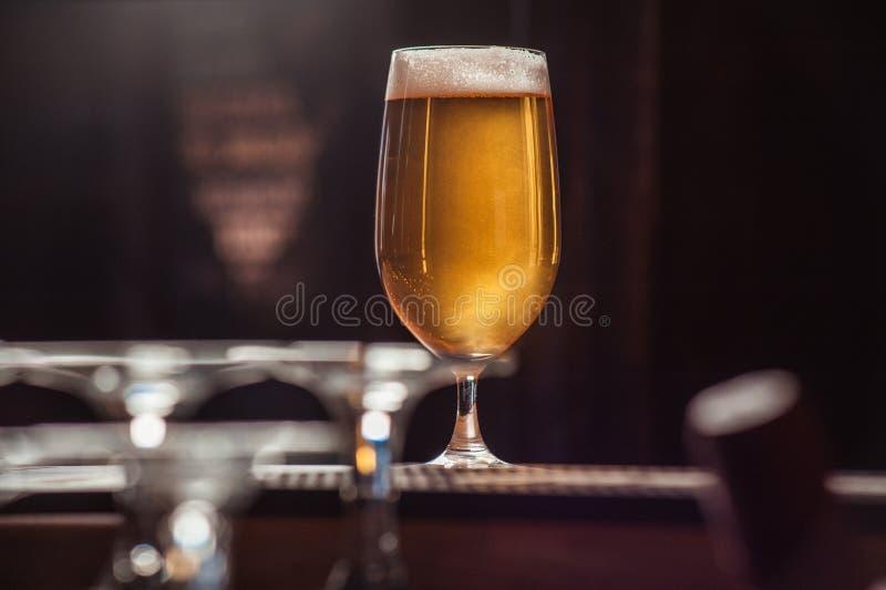 在酒吧柜台的啤酒杯 免版税图库摄影