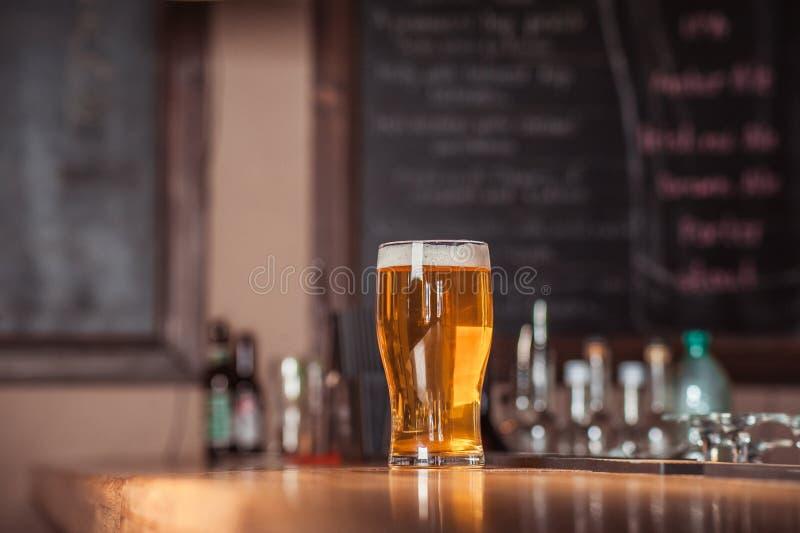 在酒吧柜台的啤酒杯 免版税库存照片