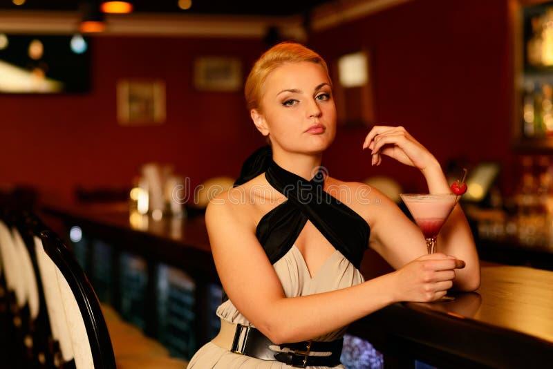 在酒吧柜台附近的美丽的白肤金发的妇女 免版税库存照片