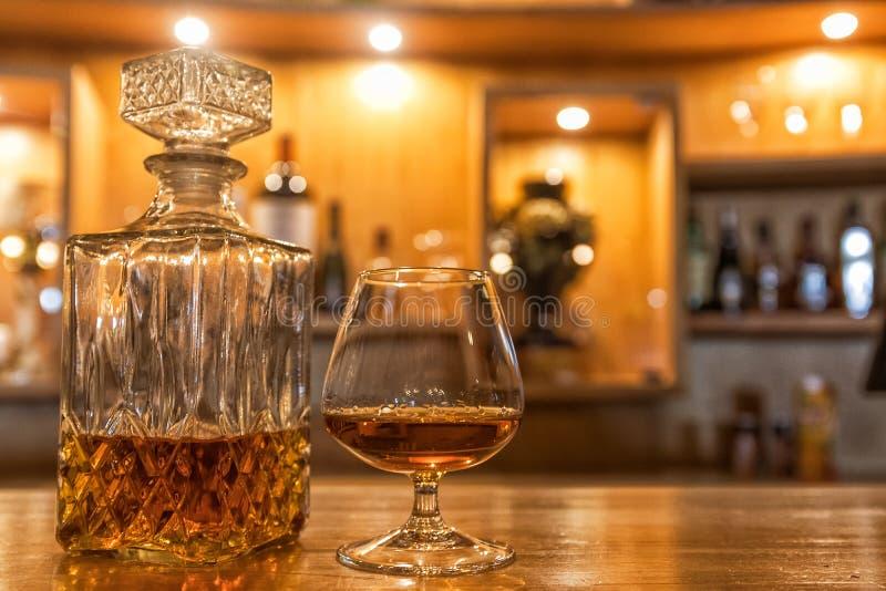 在酒吧柜台顶部的古色古香的威士忌酒瓶 库存图片