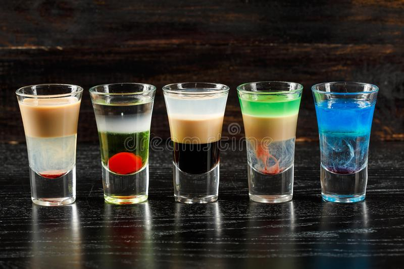 在酒吧桌,五颜六色的党饮料上的酒精鸡尾酒行 免版税图库摄影
