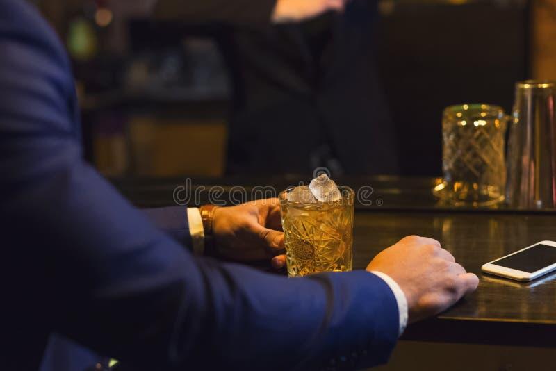 在酒吧的商人饮用的威士忌酒 库存图片