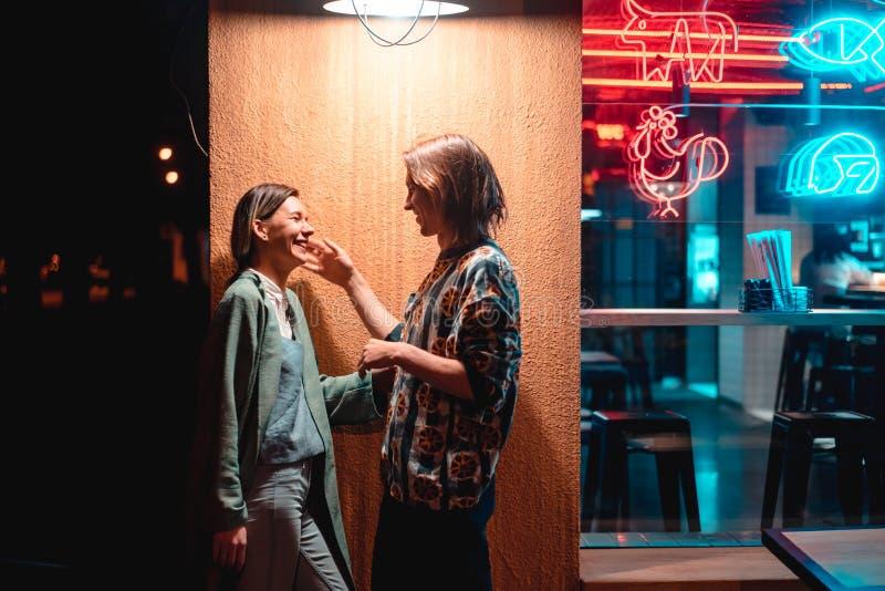 在酒吧的年轻夫妇,夜城市的街道 免版税库存照片