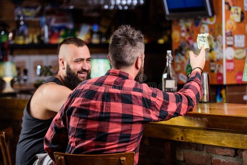 在酒吧的星期五放松 放松在客栈的朋友 行家残酷有胡子的人花费与朋友的休闲在酒吧柜台 免版税库存图片