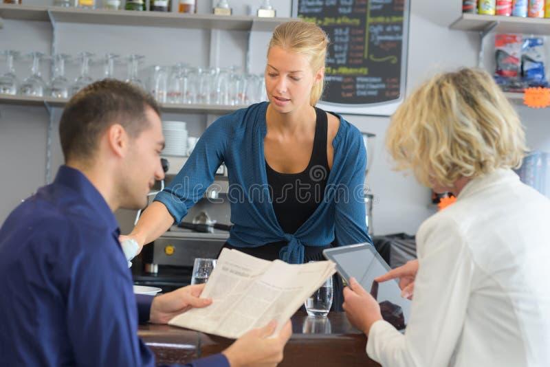 在酒吧的服务的愉快的成人 免版税库存照片