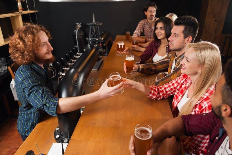 在酒吧的青年人小组,男服务员给啤酒,坐在木逆客栈顶视图,通信的朋友 免版税库存图片