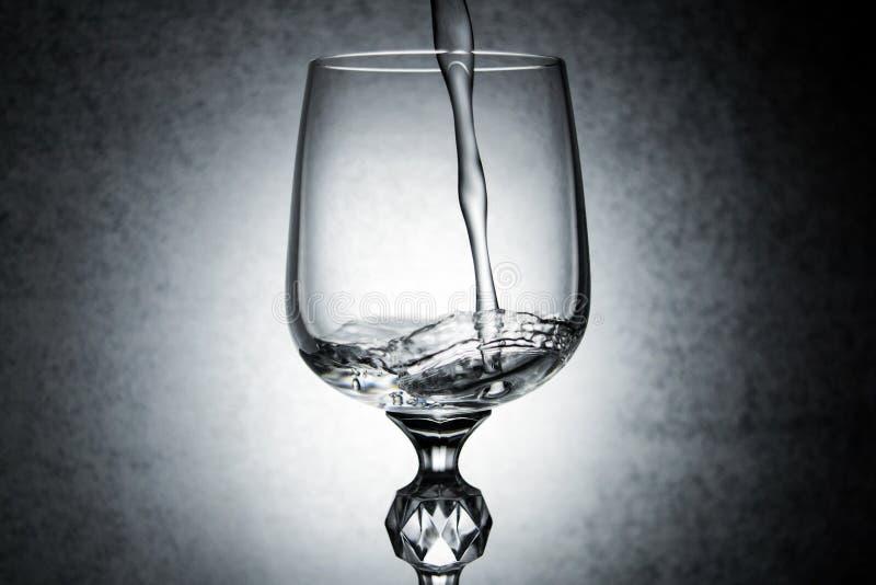 在酒杯的水飞溅 库存图片