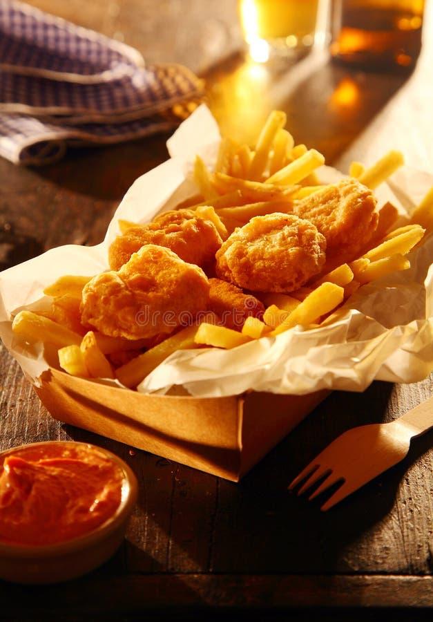 在酥脆面团的油煎的鱼用炸薯条 免版税库存图片