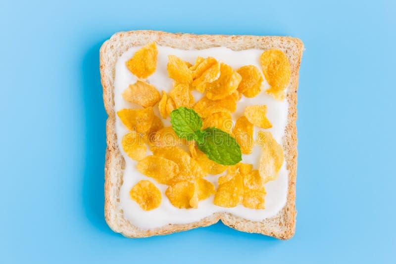 在酸奶的玉米片在面包用在蓝色淡色Bac的薄荷 库存照片
