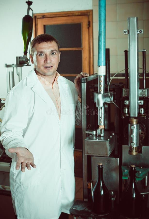 在酿酒厂检查瓶塞住的质量的工作者 库存照片