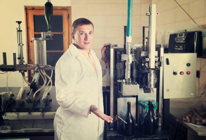 在酿酒厂检查质量的专业传动机工作者 图库摄影