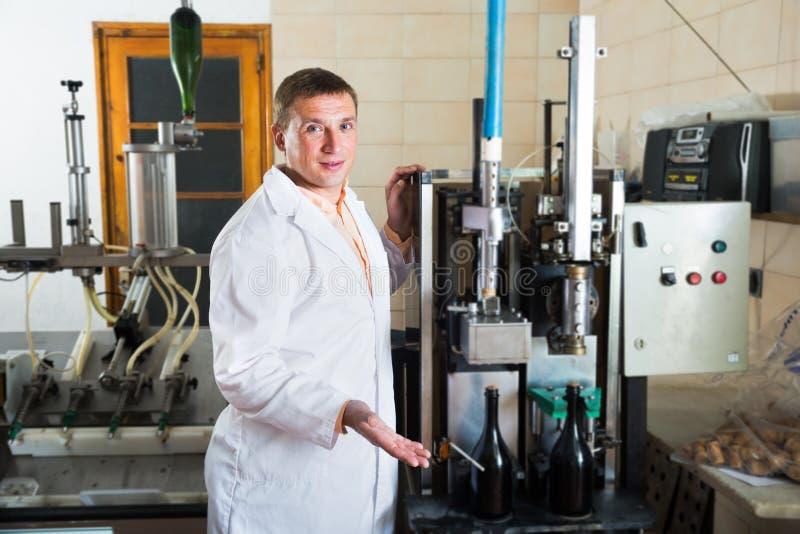 在酿酒厂检查质量的专业传动机工作者 库存图片