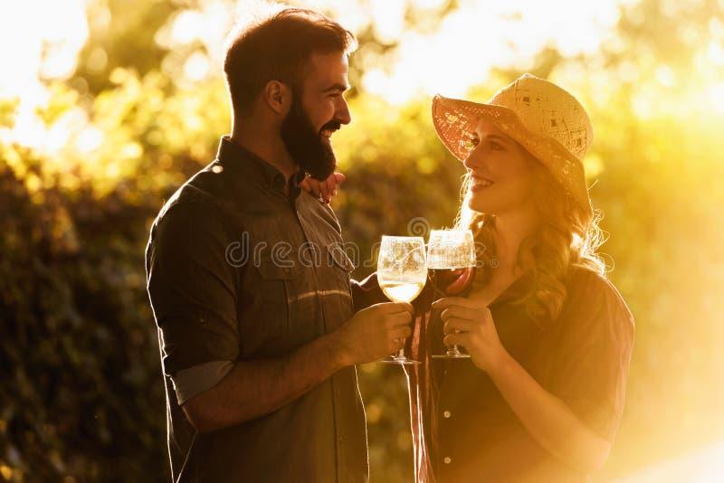 在酿酒厂葡萄园的年轻微笑的夫妇品尝酒 库存照片