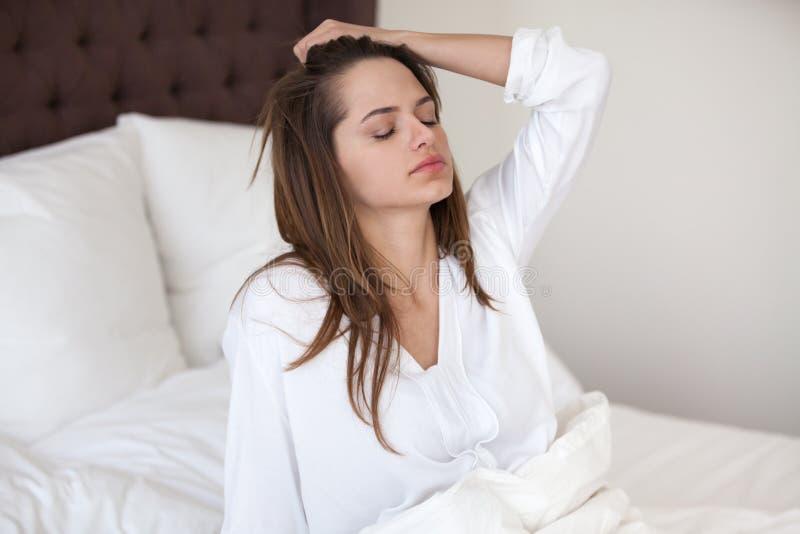 在醒的困妇女感觉宿酒头疼在床上以后 免版税库存照片
