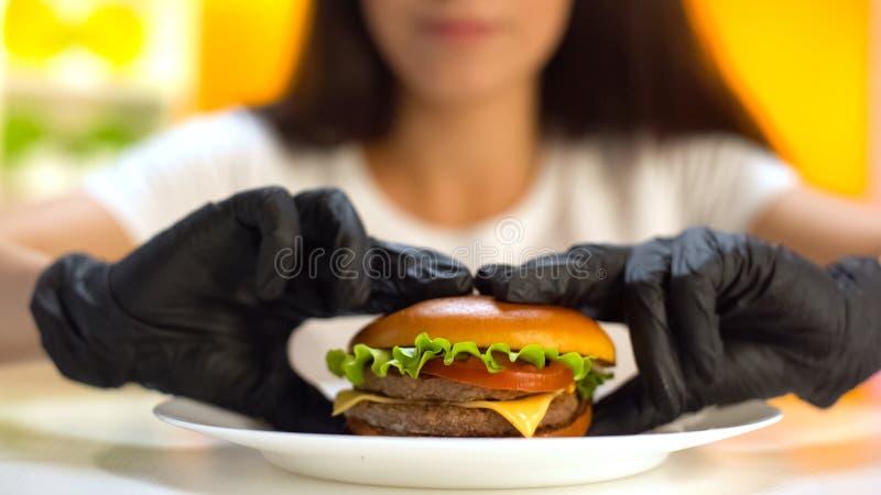 在采取从白色板材的黑橡胶手套的妇女手肥胖双重汉堡 库存图片