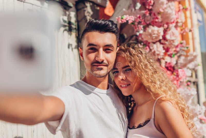 在采取在智能手机的爱的混合的族种夫妇selfie走在城市 愉快的阿拉伯男人和白人妇女在日期 免版税库存照片