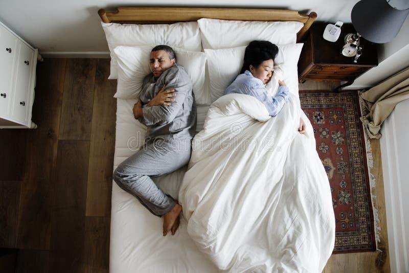 在采取所有毯子的床妇女的人种间夫妇 免版税库存照片