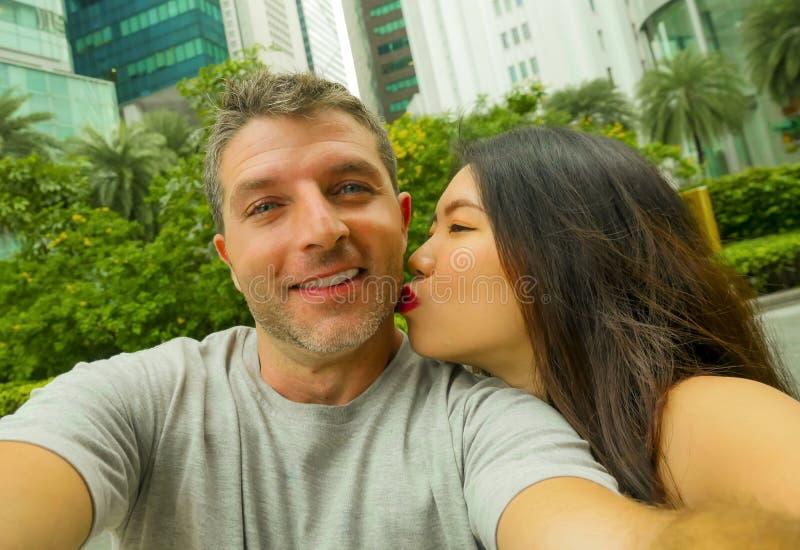在采取selfie的爱的年轻愉快和有吸引力的混杂的亚洲白种人种族夫妇生动描述一起微笑和亲吻享用 库存图片