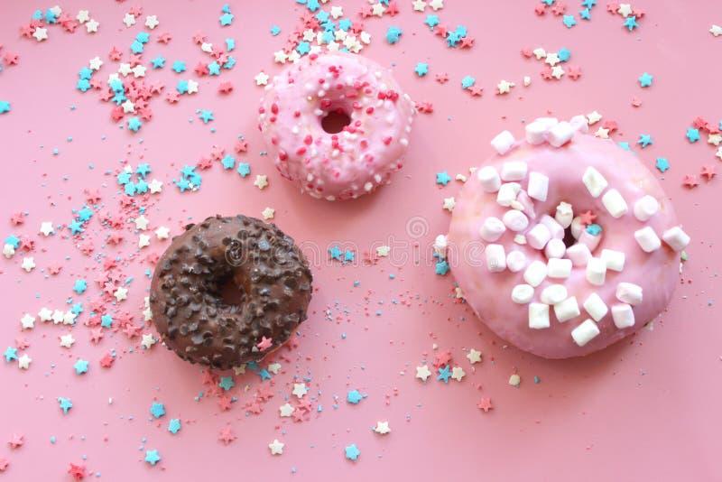 在釉的五颜六色的油炸圈饼在与多彩多姿的桃红色背景洒糖星 免版税库存图片