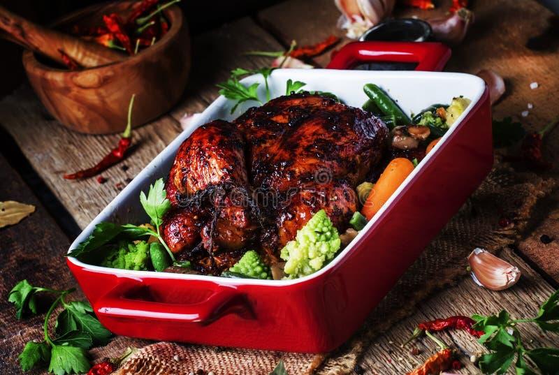 在釉的被烘烤的鸡与菜以烘烤的红色形式  免版税库存图片