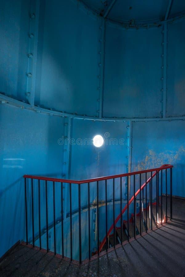 在里面的老灯塔 红色铁螺旋台阶、圆的窗口和蓝色墙壁 免版税库存图片