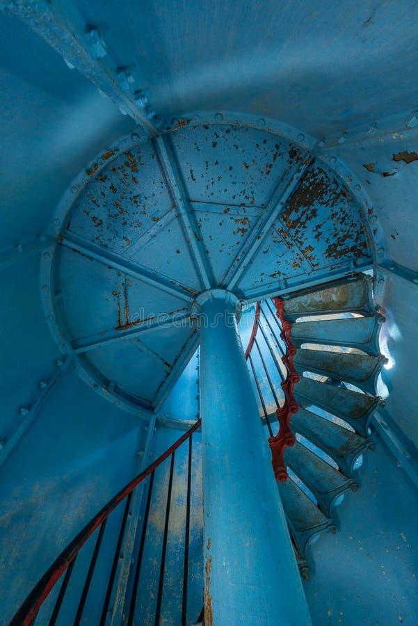 在里面的老灯塔 红色铁螺旋台阶、圆的窗口和蓝色墙壁 库存图片