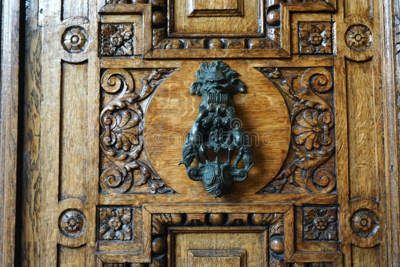 在重的被雕刻的木门的葡萄酒古色古香的通道门环 免版税库存照片