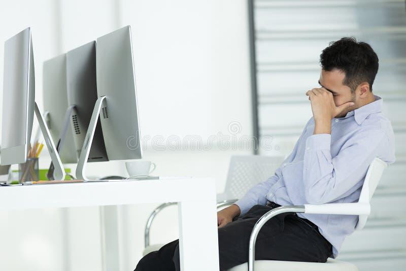 在重音的年轻商人 在现代办公室compu前面坐 库存图片