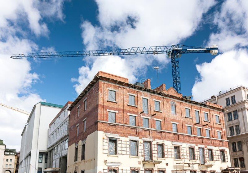 在重建下的老砖瓦房与在蓝色的塔吊 免版税图库摄影