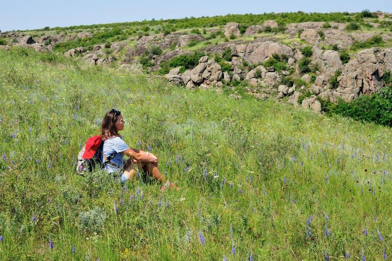 在野花中间的背包徒步旅行者 库存照片