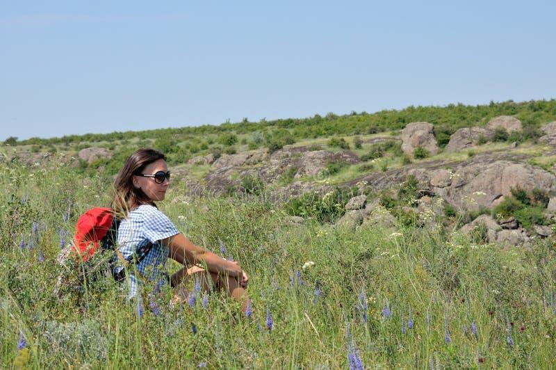 在野花中间的背包徒步旅行者 免版税库存图片