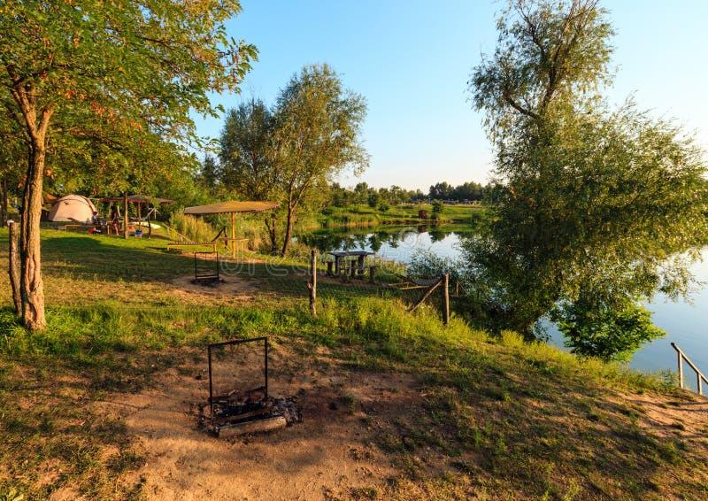 在野营的沥青的家庭在夏天湖岸附近 免版税库存图片