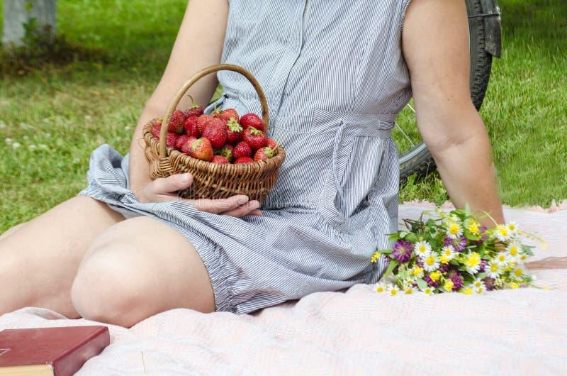 在野餐妇女坐在草的格子花呢披肩并且拿着一个篮子用红色成熟草莓和野花花束  免版税库存图片