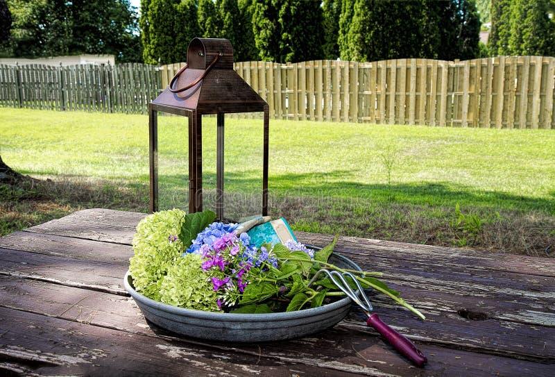 在野餐桌上的从事园艺的供应户外有花的家在盘子 免版税库存图片