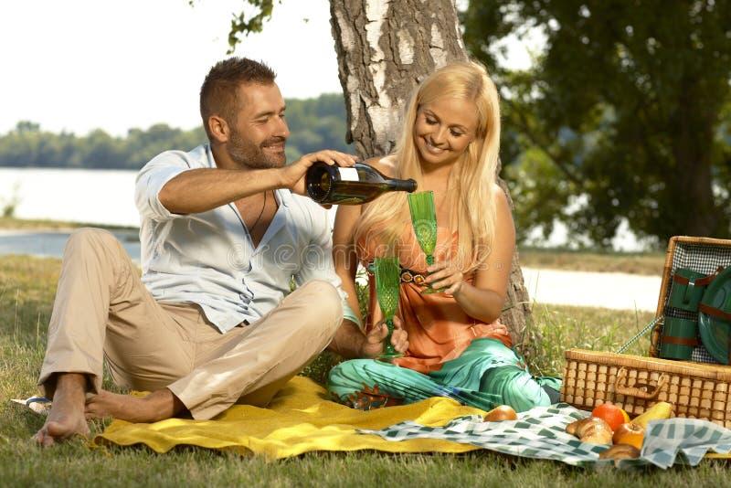 在野餐的丈夫和妻子饮用的香槟 图库摄影