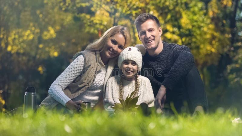 在野餐的传统家庭在公园微笑和看照相机,保险的 库存照片