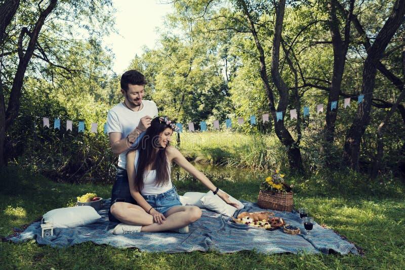在野餐的年轻夫妇坐一条毯子在人在她的顶头花冠上把放的公园 免版税库存照片