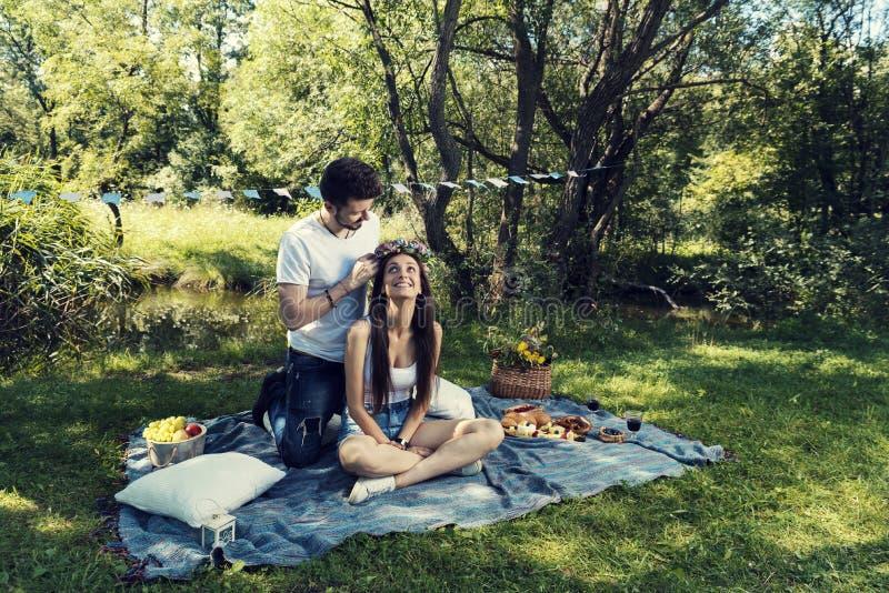 在野餐的年轻夫妇坐人在她的顶头花冠上把放的毯子 库存图片