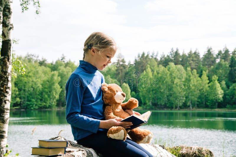 在野餐的逗人喜爱的女孩读书玩具熊书 最好的朋友坐森林湖下落的树  温暖葡萄酒定调子 免版税库存图片